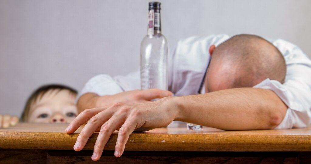mężczyzna z butelką alkoholu i dziecko