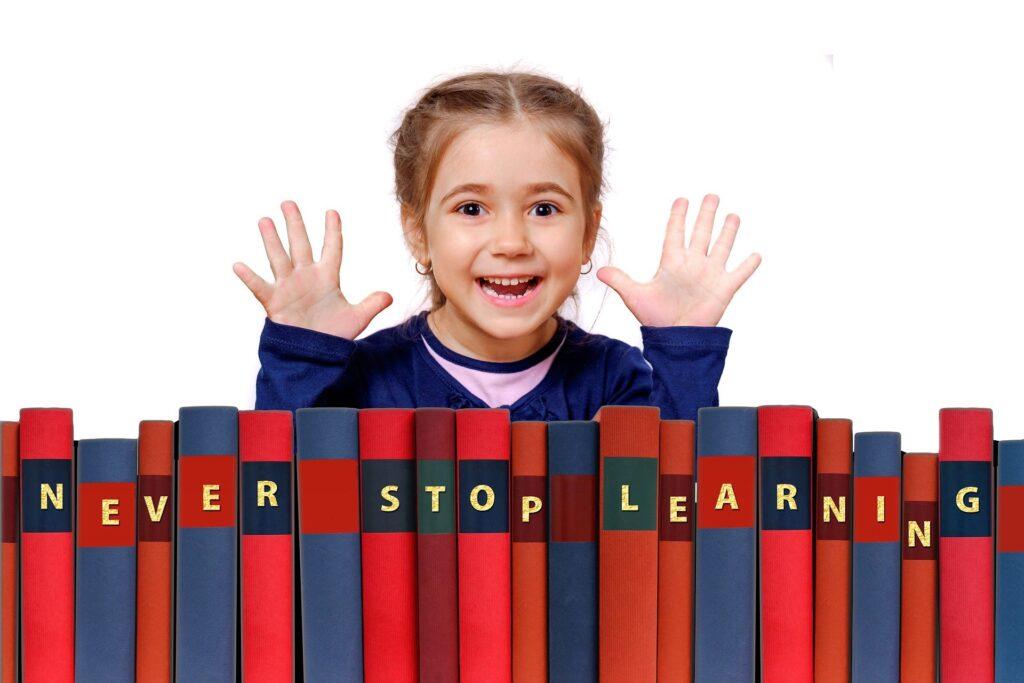 uśmiechnięta dziewczynka otoczona książkami