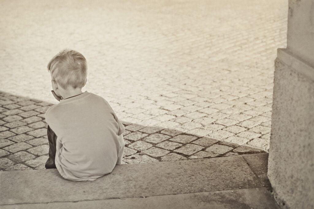 chłopiec siedzący na schodach