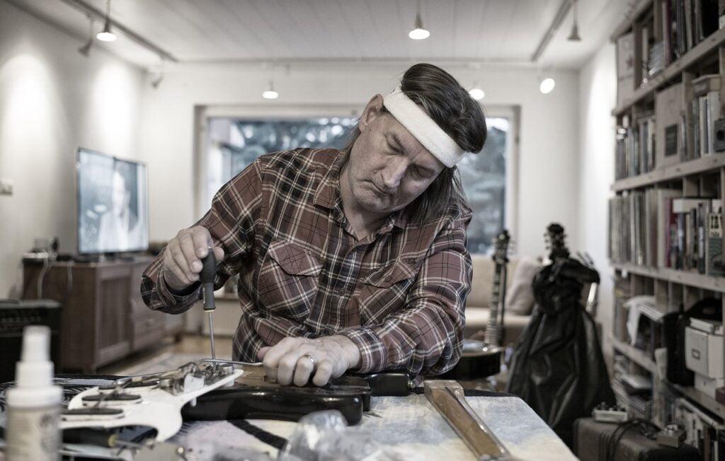Mężczyzna naprawia gitarę w pracowni.