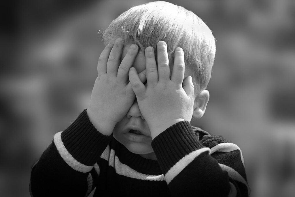 mały chłopczyk zakrywa twarz rękami