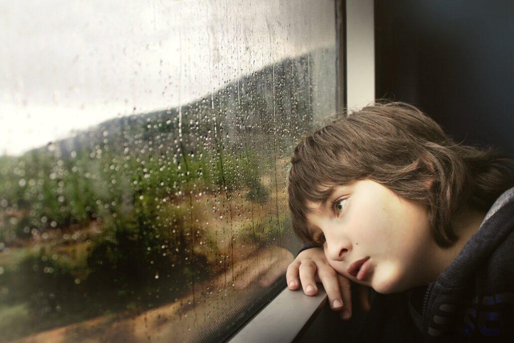 zamyślony chłopiec patrzy przez mokre od deszczu okno