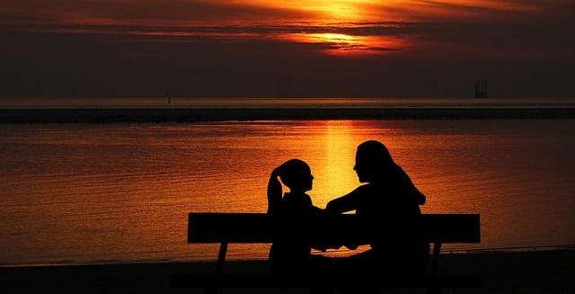 kobieta i dziewczynka rozmawiają na ławce nad wodą o zachodzie słońca